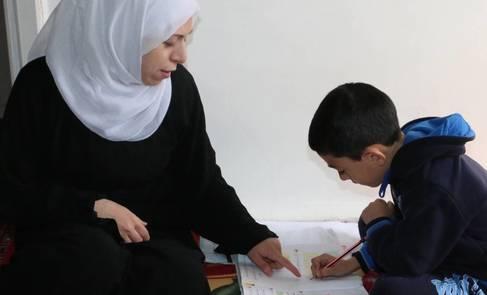 Palestine refugee woman teaches her son during COVID-19 school closures. © 2020 UNRWA Photo