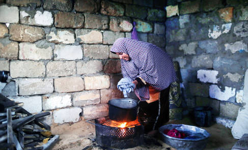 Like so many in Gaza, a Palestine refugee in Beach refugee camp, western Gaza City, uses the only means at her disposal to cook, wash clothes and heat her home. © 2017 UNRWA Photo by Tamer Hamam