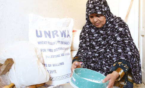 A refugee woman from Beach camp, Gaza, is using flour after receiving her food assistance. ©2018 UNRWA, Photo by Khalil Adwan.