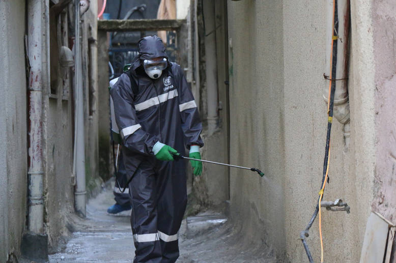 "UNRWA sanitation workers wearing protective health gear in the Aida Refugee Camp perform a sterilization of the camp's streets and buildings. UNRWA has stepped up its sterilization efforts in the 19 refugee camps across the West Bank, performing regular cleanings of the camps streets and UNRWA facilities. Adam Baraqa'a, one of the sanitation workers and a resident of the Beit Jibreen camp, says that while the coronavirus pandemic has been a scary time, ""I feel proud that I can do something to help protect my community, and I feel safe while doing it because of the protective gear that UNRWA has provided us with.""  © 2020 UNRWA Photo by Yumna Patel"