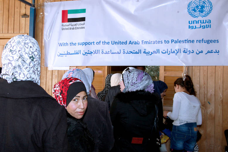 Palestine refugees from Damascus queue at the UNRWA Alliance Distribution Centre to receive food packages, made possible by the generous support of the United Arab Emirates. Damascus, November 2014. © 2014 UNRWA Photo by Taghrid Mohammad