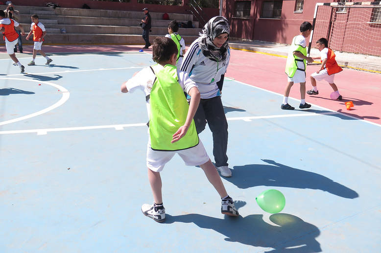 A teacher trained by the Real Madrid Foundation coaches students in a balloon activity designed to improve football coordination skills. Kalandia Training Centre, West Bank. © 2015 UNRWA Photo by Ruba Hafayda