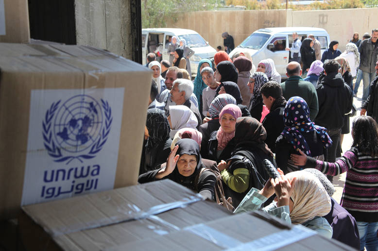 Beneficiaries queue for food assistance at the UNRWA distribution centre in Sahnaya, Damascus. More than 95 per cent of the 480,000 Palestine refugees remaining in Syria rely on UNRWA for their minimum daily needs. Generous support from the UAE meant that UNRWA was able to distribute food assistance to more than 460,000 Palestine refugees in 2014 and 2015. © 2015 UNRWA Photo by Taghrid Mohammad