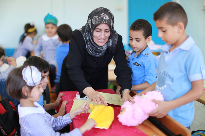 """[The Education Reform] has a positive impact on changing my pedagogy as a teacher – we started using group-work, drama, and role-play in teaching, which has positively impacted the conduct and level of achievement of the children,"" explains Raja Murjan, a basic elementary teacher in Gaza, who has been teaching for 20 years. © 2016 UNRWA Photo by Rushdi al-Sarraj"