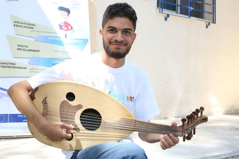"""يقول أحمد البالغ من العمر 23 عاما في سنته الرابعة في كلية الهندسة الزراعية في دمشق: """"الموسيقى تجعلك تشعر بالرضا والسعادة""""، وقد  اتجه إلى الموسيقى للتغلب على المشقة التي واجهها أثناء الصراع. ويقوم هو وصديقه أحمد بتعليم الموسيقى للأطفال الذين تتراوح أعمارهم بين 6 و 12 عاما لتوفير الراحة لهم من ضغوط الحرب. مركز تدريب دمشق، سورية. الحقوق محفوظة للأونروا 2017، تصوير تغريد محمد"""