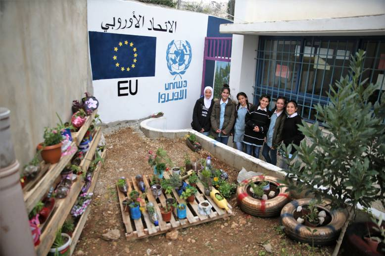 Wooden crates, recycled pots and tires house budding plants at the Birzeit Girls' School new garden thanks to the EU-UNRWA Healthy Living, Healthy Spaces initiative. Students stand proudly in front of their new garden, showing off the fruits of their labour. © 2018 UNRWA Photo by Dina Sharif