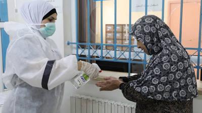 موظف من الطاقم الصحي في الأونروا يساعد مريضا من لاجئي فلسطين في مركز الأمعري الصحي في الضفة الغربية. © 2020 صور الأونروا