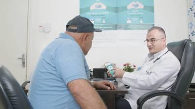 """طبيب في مركز النزهة الصحي في عمان ، الأردن يشرح لمريض يعاني من مرض غير معدي (NCD) حول كيفية استخدام تطبيق الهاتف الذكي NCD الذي تم إصداره حديثًا """"صحتك مع الأونروا"""" وكيف يرتبط بصحته الإلكترونية سجل في نظام الأونروا للصحة الإلكترونية. © 2020 الأونروا تصوير جورج عواد"""