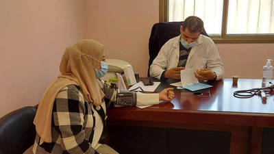 Palestine refugee mobile clinic volunteer, Saeda Qaba'h receives a medical consultation. © 2021 UNRWA Photo