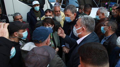 UNRWA Commissioner-General Philippe Lazzarini, center right, is seen listening to a Palestine refugee during a visit to the Ein el-Hilweh Palestine refugee camp in Lebanon on 30 March 2021. © 2021 UNRWA Photo