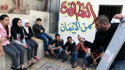 """محمد، وهو أحد المتطوعين لدى الأونروا، يعمل على إشراك لاجئي فلسطين الشباب في المركز الجماعي بمدرسة حيفا في دمشق من أجل مكافحة العنف المبني على النوع الاجتماعي وذلك كجزء من مبادرة """"الأمان من البداية"""" الممولة من قبل الولايات المتحدة. الحقوق محفوظة للأونروا، 2016. تصوير تغريد محمد"""