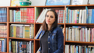Ro'a Sheesh photographed in the library of her childhood UNRWA school. © 2019 UNRWA Photo by Abeer Ismail.