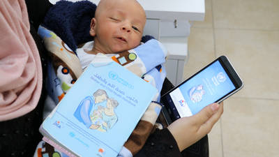 A Palestine refugee mom with her newborn baby on her lap scrolls through the UNRWA Mother and Child application while waiting her turn to see the doctor at the Baq'a Health Centre in Amman, Jordan © 2019 UNRWA Photo by Shafiq Fahd