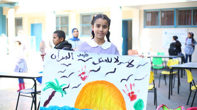 "A student at the UNRWA Rimal Preparatory Girls' School ""A"" in Gaza shows off her artwork at a GBV awareness raising event. © 2019 UNRWA photo by Ibrahim Abu Usheiba"