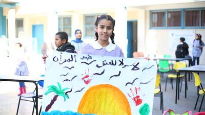 """طالبة في مدرسة رمال الإعدادية للبنات """"أ"""" في غزة تستعرض أعمالها الفنية لدى انطلاقة حملة الأيام الستة عشرة للعمل ضد العنف المبني على النوع الاجتماعي. الحقوق محفوظة للأونروا لعام 2019 ، تصوير إبراهيم أبو عشيبة"""