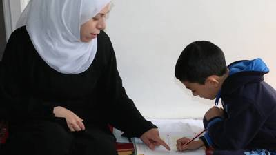 Palestine refugee woman teaches her son during COVID-19 school closures. © 2020 UNRWA Photo