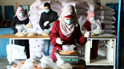 Palestine refugees employed through the UNRWA Cash-for-Work programme pack food items at the Beach Distribution Centre in Gaza during the COVID-19 pandemic. © 2020 UNRWA Photo by Khalil Adwan