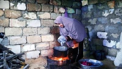 لاجئة فلسطينية في مخيم الشاطئ، غرب مدينة غزة، على غرار العديد من أهالي غزة، تستخدم الوسائل الوحيدة المتاحة لها للطهي وغسل الملابس وتدفئة بيتها. © 2017، الأونروا، تصوير تامر حمام.