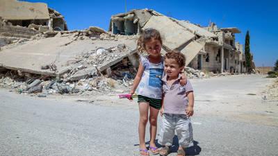 طفلان يقفان أمام مبنى مدمر في مخيم عين التل. © 2018 الأونروا، تصوير: أحمد أبو زيد