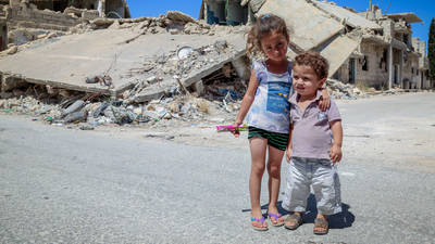 Palestine refugee children stand in front of a destroyed building in Ein el Tal camp in Syria. © 2018 UNRWA Photo by Ahmad Abou Zeid