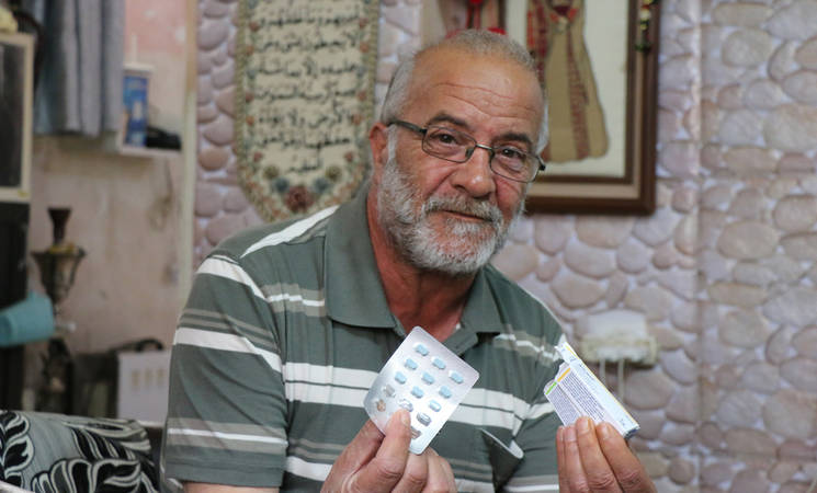Abdulrahman Abu Srour holds up his medications for diabetes and blood pressure that he receives from the UNRWA clinic in Bethlehem. © 2020 UNRWA Photo by Yumna Patel