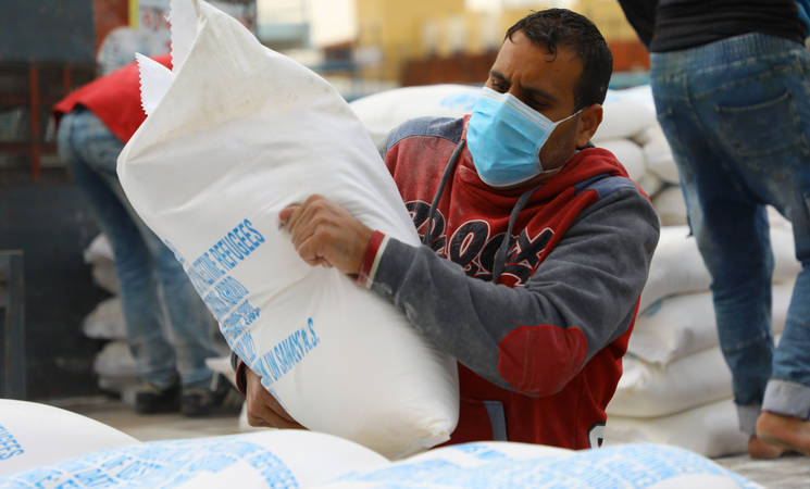 An UNRWA food distribution for Palestine refugees in Gaza during the COVID-19 pandemic. In an attempt to maintain a high level of safety and prevent the spread of COVID-19, the Agency carried out distribution of food aid through home deliveries. ©️ 2020 UNRWA Photo by Khalil Adwan
