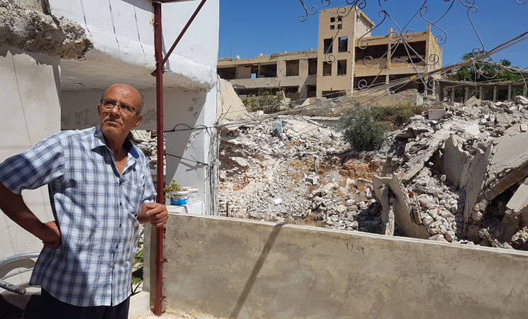 Hajj Ma'rouf stands in front of the remains of his damaged home in Ein el Tal, Syria. © 2020 UNRWA photo by Suzanne Leuenberger