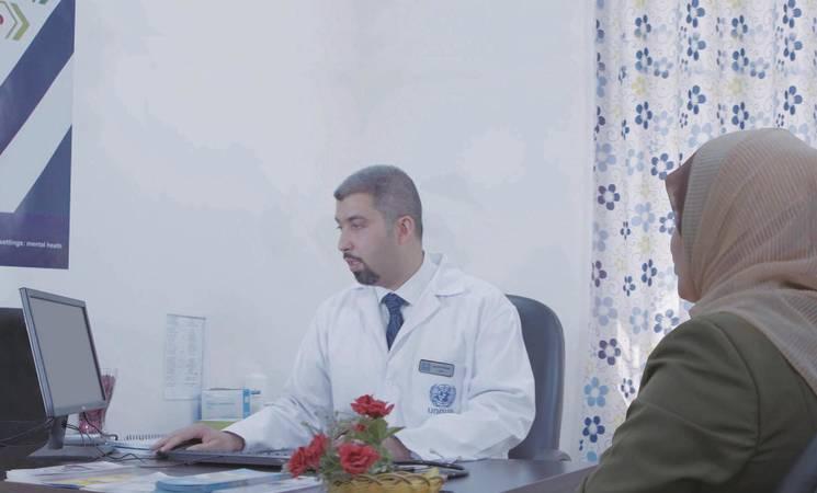 الدكتور أسامة الحاج علي ، المسؤول الطبي في مركز البقعة الصحي الرئيسي التابع للأونروا في الأردن خلال استشارة طبية لمريض. © 2020 الأونروا تصوير جورج عواد