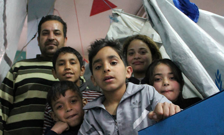 A family in their living space in Doumar shelter, Damascus. Thirteen UNRWA schools have been converted into UNRWA shelters.