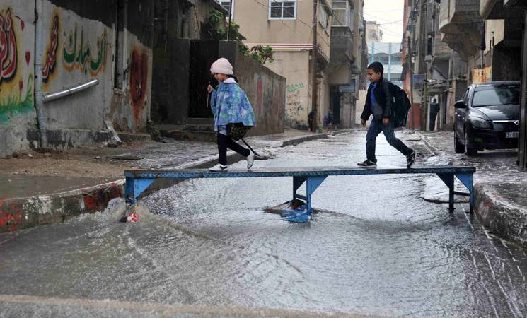 Children crossing a flooded street in Gaza City