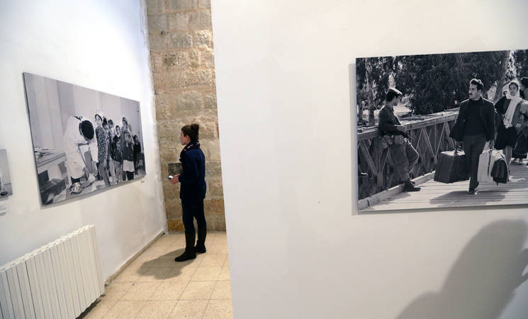 A woman browses through the selection of photos at the exhibition. © UNRWA Photo by Alaa Ghosheh