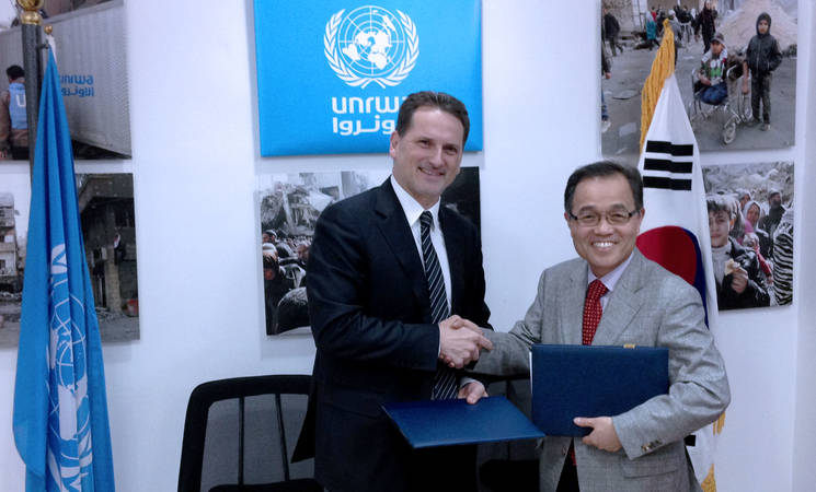 "UNRWA Commissioner-General Pierre Krähenbühl (left) and The Vice President of the Korea International Cooperation Agency (KOICA) Doo Jung Soo shake hands after the signing of an agreement to support the ""Gaza Gateway"", a social enterprise for outsourcing employment. © UNRWA Photo"