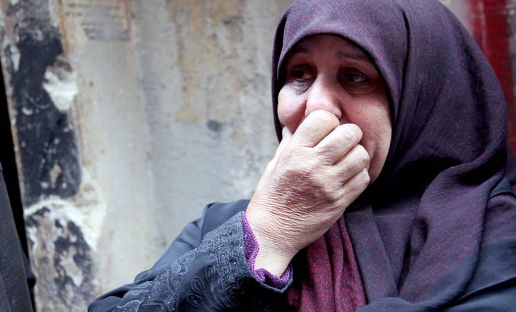 A woman weeps during an UNRWA food distribution in March 2015. UNRWA has been unable to access Yarmouk to provide humanitarian assistance since 1 April 2015. © 2015 UNRWA Photo by Taghrid Mohammad