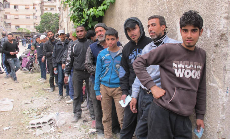 Men and boys queue to receive assistance at the distribution area in Yalda, 15 April, 2015 ©UNRWA