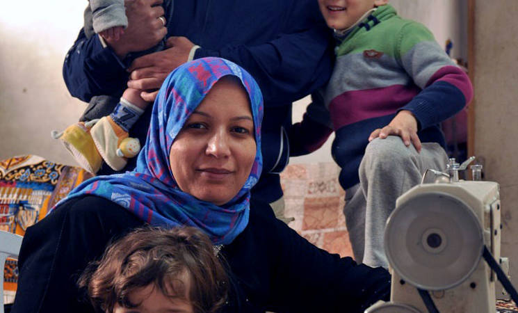 Sameera and her family with her new sewing machine. © 2015 UNRWA Photo