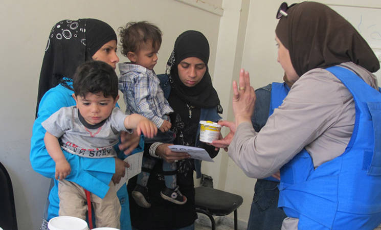 UNRWA medical personnel distribute WFP nutritional supplements to displaced civilians, Yalda, 30 April, 2015 © 2015 UNRWA Photo