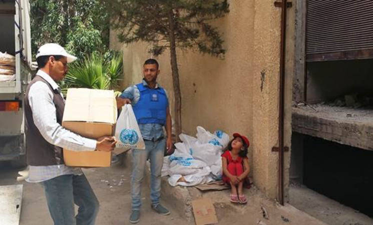 UNRWA food parcels and bread are distributed in Yalda, 7 June 2015. © 2015 UNRWA Photo