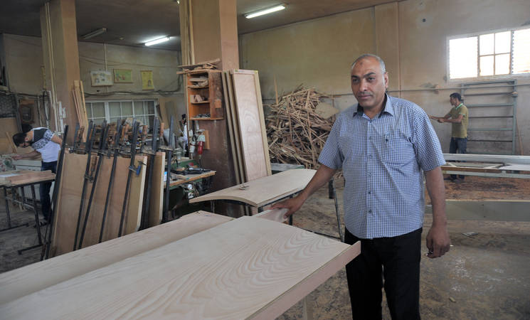 Manager Mujahed Mahmoud al-Sosi is contemplating the work of his employees in his furniture factory in Jabalia, northern Gaza. Photo credit: © 2015 UNRWA Photo by Khalil Adwan
