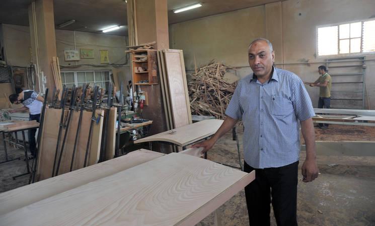 مدير المعمل مجاهد محمود السوسي يقوم بفحص عمل موظفيه في مصنع الاثاث الخاص به في جباليا، شمال غزة. جميع الحقوق محفوظة/الأونروا، عدسة:خليل عدوان