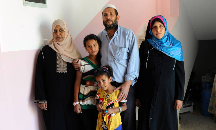 """In this house, we can invite guests and offer them tea,"" said Nabil Abu Musa about his family's new home in the Khan Younis Rehousing Project. Nabil co-signed the undertaking together with Fatheia (left) and Khadra (right), his two wives. © 2015 UNRWA Photo by Khalil Adwan."