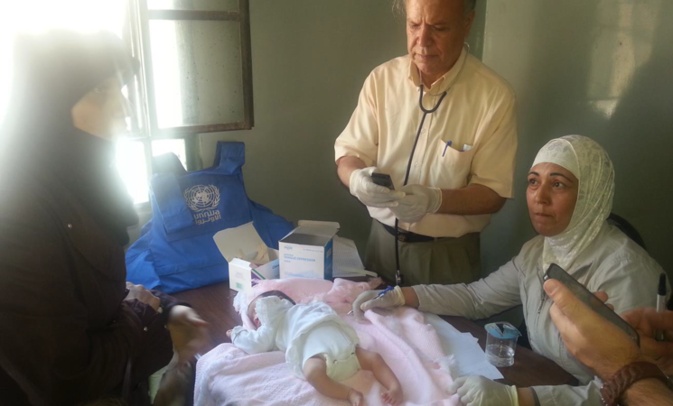 UNRWA medical staff examine a baby in Yalda, 3 September 2015. © 2015 UNRWA Photo