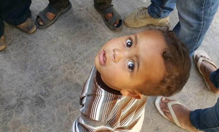A child waits outside the UNRWA health point in Yalda. © 2015 UNRWA Photo