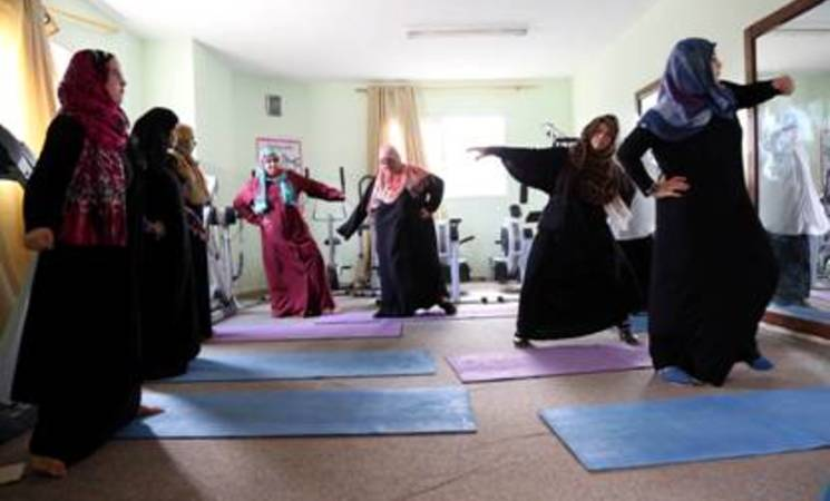 A group of women practice yoga at the gym in the Rawafed Association in Deir El-Balah, central Gaza. The sports facilities are funded by the UNRWA Gender Initiative. © 2015 UNRWA Photo by Khalil Adwan