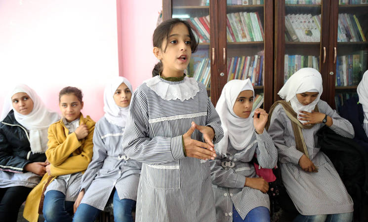 "A group of students from al-Maghazi Preparatory Girls School B attend an awareness session on early marriage at al-Maghazi WPC. One student, Raghda Abu Ma'liq, explains her point of view during discussions: ""Education is really important for us; it's the tool to achieve a better understanding of things, which at the end will lead to a better future too."" © 2015 UNRWA Photo by Tamer Hamam"