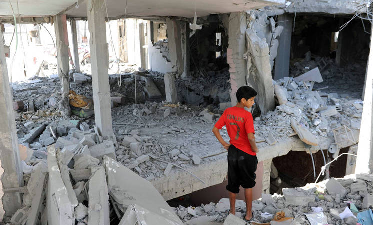 Palestinians inspect the remains of a house which was destroyed during an air strike in Central Bureij refugee camp, in the Middle Area of the Gaza Strip, 15 July 2014. © 2014 UNRWA Photo by Shareef Sarhan