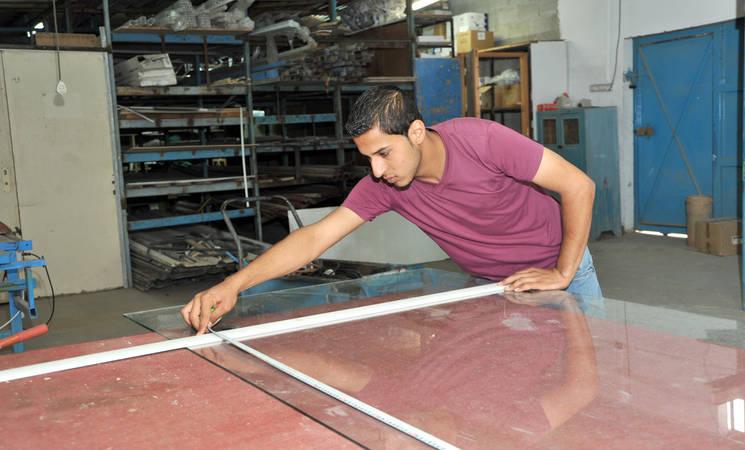 Twenty-year old Fares Sani is measuring window glass before cutting it, in Gaza. © 2015 UNRWA Photo by Khalil Adwan