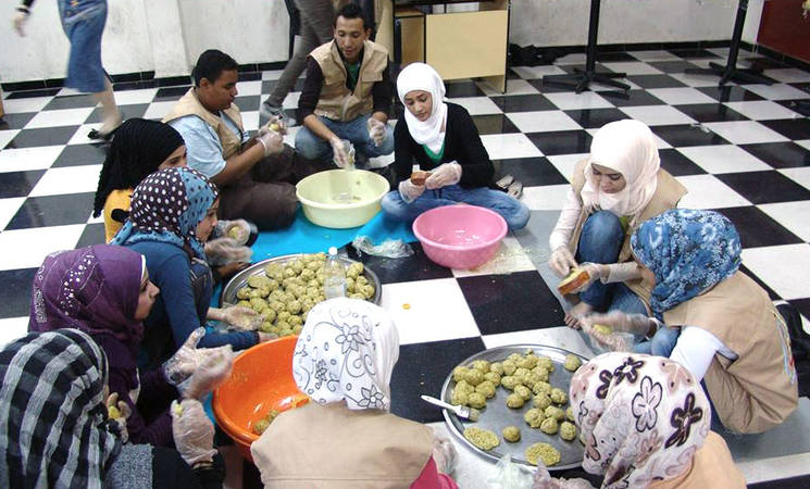 Young volunteers prepare ma'moul for Jaramana residents