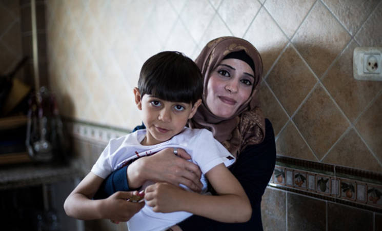 Thirty-six-year-old Hayam Farahat holding her son, 6-year-old Ali, in their home in Rafah, southern Gaza. © 2016 UNRWA Photo by Tamer Hamam