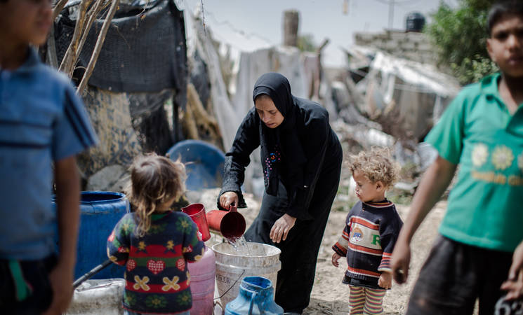 """Sometimes many days pass and we can't wash the laundry. The children get scabies and lice,"" said Salwa Abu Nemer, who lives with her family in a makeshift shelter in Khan Younis, southern Gaza. Salwa's home, like those of many people in Gaza, is not connected to the municipal water network. © 2016 UNRWA Photo by Tamer Hamam"