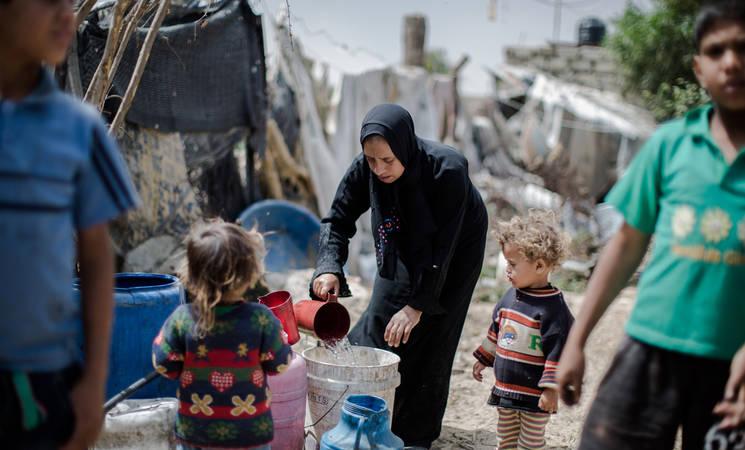 """"""" في بعض الأحيان تمر الأيام ولا يمكننا غسيل الملابس. أصيب الأطفال بالقمل والجرب"""" قالت سلوى أبو نمر التي تعيش مع أسرتها في مأوى مؤقت في خان يونس جنوب قطاع غزة. منزل سلوى كمنزل العديد من سكان غزة غير مرتبط بشبكة المياه البلدية. جميع الحقوق محفوظة: الأونروا غزة 2016، تصوير تامر حمام."""